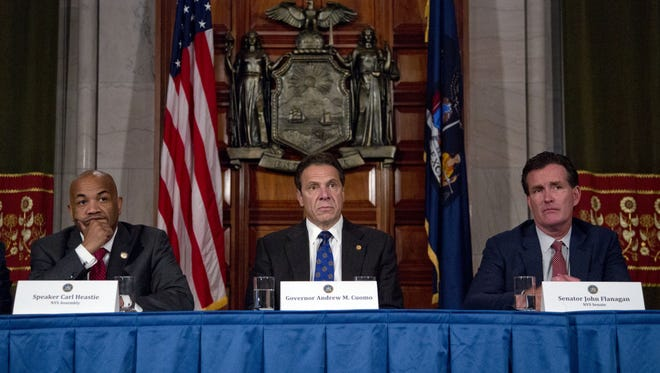 Assembly Speaker Carl Heastie, D-Bronx, left, Gov. Andrew Cuomo and Senate Majority Leader John Flanagan, R-Smithtown, during a news conference.