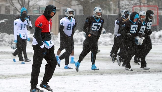 Carolina Panthers quarterback Cam Newton, left, walks across a practice field covered in snow and ice, Friday, Jan. 22, 2016, in Charlotte, N.C.