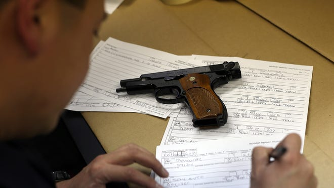 A San Francisco police officer documents a gun that was surrendered during a buy-back program in 2012.