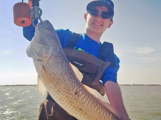 Cameron Pape, 13, caught and released this oversized redfish while fishing in Baffin Bay with his dad, Kyle Pape.