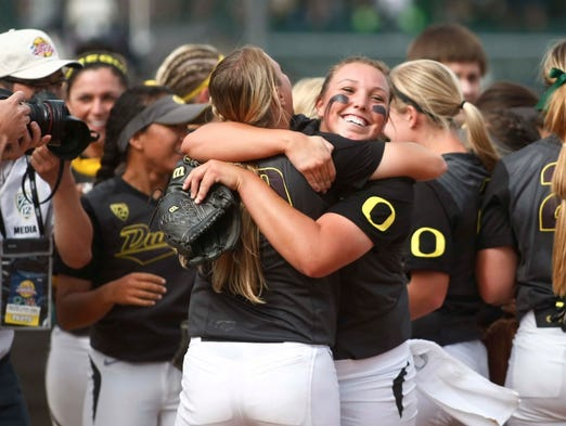Oregon starter  Cheridan Hawkins (center) celebrate with a teammate after the Ducks' 6-2 victory over  Minnesota to sweep the NCAA Eugene softball super regional at Howe Field, in Eugene, on Sunday  May 25, 2014.