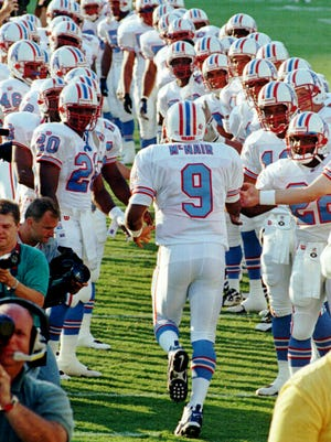 Tennessee Oilers quarterback Steve McNair (9) runs throurgh a tunnel formed by his teammates as he is introduced before the team's first game in their new state Aug. 2, 1997. The Oilers are playing the New Orleans Saints in Memphis, where they will play their first two seasons before moving into their new stadium in Nashville.