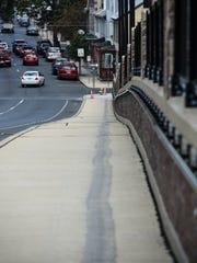 A skid mark on the sidewalk along North Ninth Street