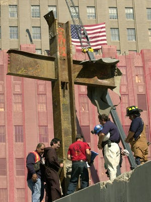 Father Brian Jordan, second from left, blesses, Thursday, Oct. 4, 2001, a cross of steel beams found amidst the rubble of the World Trade Center by a laborer two days after the collapse of the twin towers. The cross was from World Trade tower One, and was found in World Trade building Six and moved to its present location Wednesday. Other rescue and construction workers join Jordan for the ceremony.
