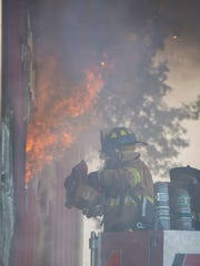 A firefighter cuts a hole in the side of a barn as fire crews battle a two-alarm fire in the 100 block of west Market Street in Jonestown on Tuesday, Feb. 14, 2017.