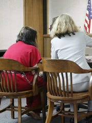 Katlyn Kinateder sits with her attorney during her