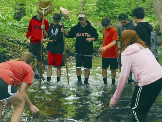 Palmyra students use a kick-net to catch macro invertebrates and analyze stream quality during an Outdoor Education class at Camp Swatara.