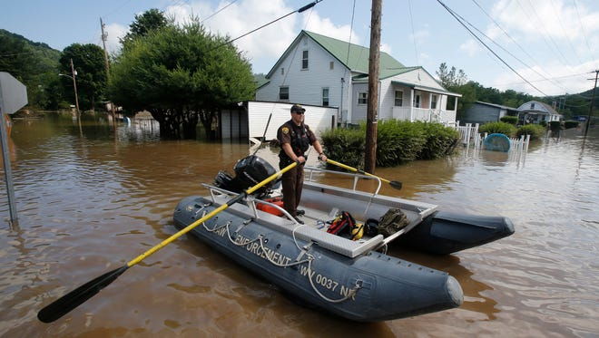Lt. Dennis Feazell, of the West Virginia Department of Natural Resources, rows his boat as he and a co-worker search flooded homes in Rainelle, W. Va., Saturday, June 25, 2016.  About 32,000 West Virginia homes and businesses remain without power Saturday after severe flooding hit the state. The West Virginia Division of Homeland Security and Emergency Management also said Saturday that more than 60 secondary roads in the state were closed.