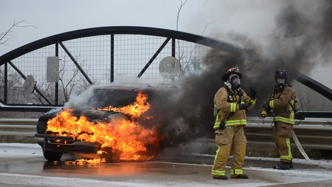 Battle Creek firefighters wait for water pressure before fighting a vehicle fire after a crash Thursday on M-66.