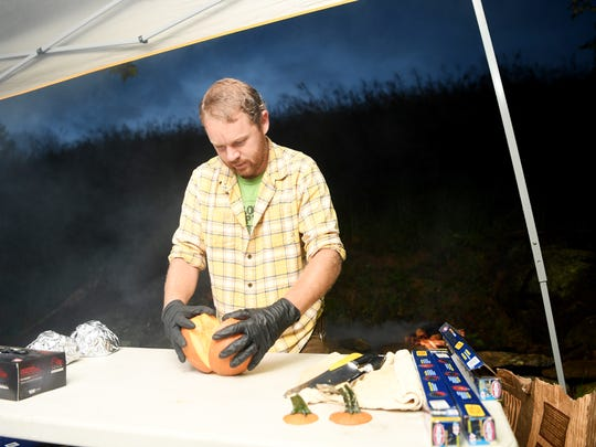 Michael Rayburn cuts open a pumpkin on the morning of September 6, 2017 as he prepares to roast pumpkins for Hillman Beer.