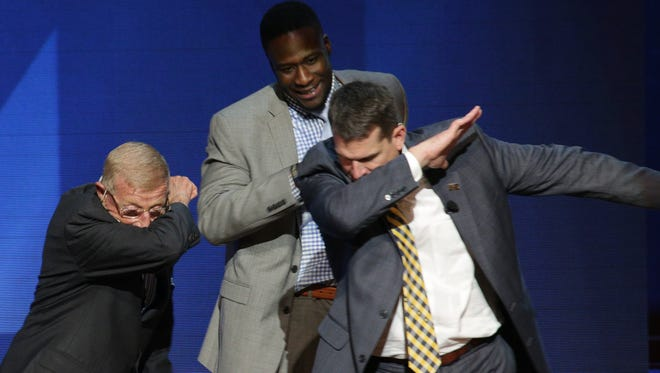"""Former Notre Dame football coach Lou Holtz, left, former Michigan quarterback Devin Gardner, center, and U-M football coach Jim Harbaugh do """"the Dab"""" at """"Signing of the Stars"""" at Hill Auditorium on Wednesday, Feb. 3, 2016."""