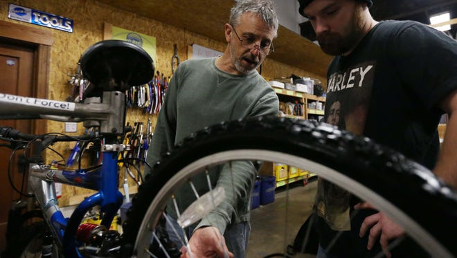 Dan Baldi, a manager at the Des Moines Bike Collective, gives advice and instruction to others working on bikes in the shop on Thursday morning, Feb. 25, 2016, in the East Village.