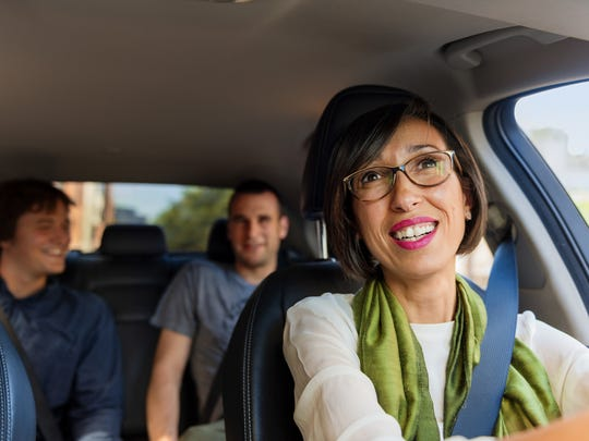 A woman glancing at passengers in the rearview mirror while driving