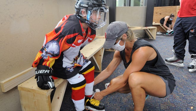 Sarah Argentieri, of Shrewsbury, laces up the skates of her 9-year-old son, Orazio, in a new socially distanced area in the lobby of the New England Sports Center in Marlborough.