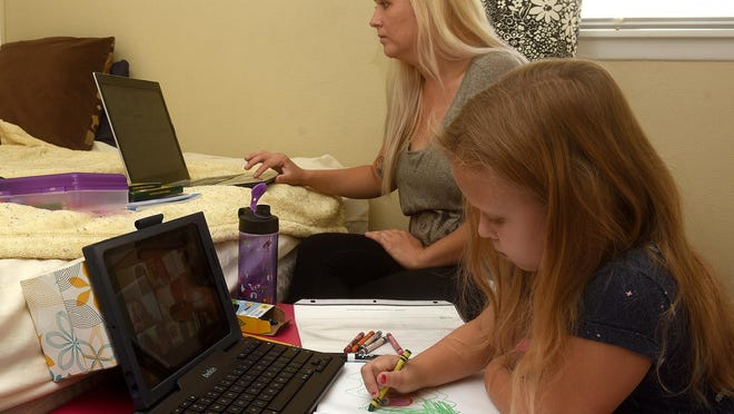 Stephanie Day works from home as her daughter Hayden, 5, draws a tiger during Parkade Elementary School kindergarten class by computer from their home.