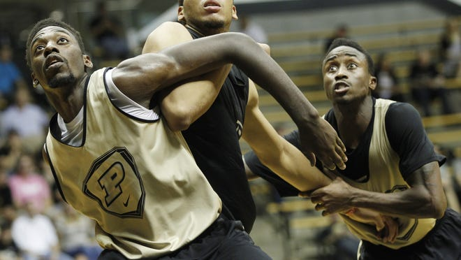 Jacquil Taylor, left, and Jon Octeus, right, work to keep A.J. Hammons out of rebounding position as Purdue men's basketball holds its second scrimmage Saturday, October 25, 2014, in Mackey Arena.