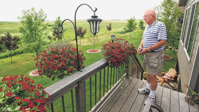 Larry Sorensen looks at the land behind his home facing south from Whisper Ridge on July 25.
