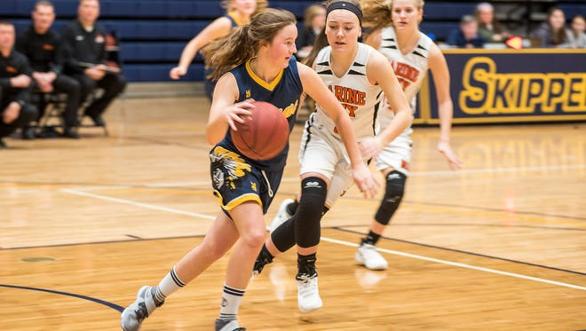 Capac's Alexis Anderson (left) drives the ball around Marine City's Lauren Morris during their SC4 Holiday Girls' Basketball Showcase match Dec. 28.