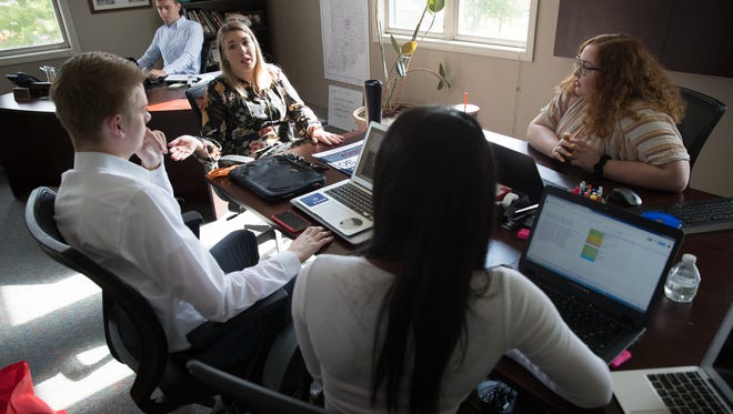 Stephanie Perry (at head of table), Assistant Director of Public Relations for Fishers, leads interns in a meeting at the office of Scott Fadness, the mayor of Fishers, Wednesday, June 20, 2018. The mayor, who has an office that contains a meeting table, has moved into a hallway, and allowed Summer interns to populate his office.