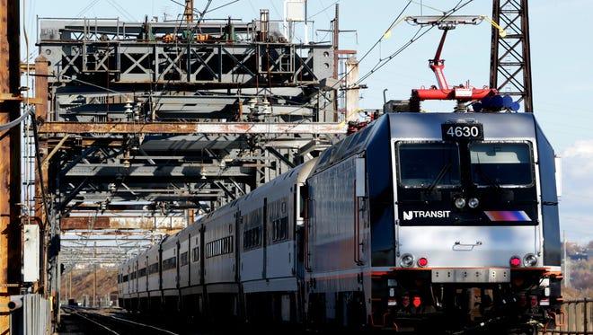 A New Jersey Transit train travels across the Portal Bridge in Kearny.
