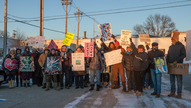 Community members gathered for a peaceful march across the Michigan Street Bridge to protest President Donald Trump's plan and policies Thursday, Feb. 2, 2017.