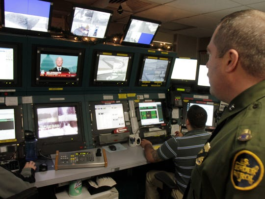 A Border Patrol agent looks over security screens in