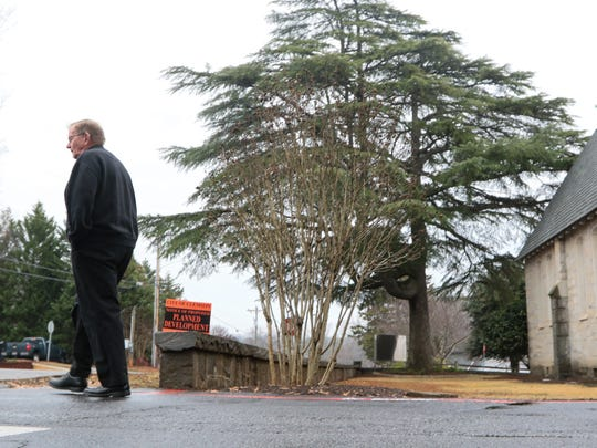 Father Dan McLellan of Saint Andrew Catholic Church in Clemson walks by an orange sign from the city of Clemson that is a notice of proposed planned development of the church at Sloan and Edgewood streets in Clemson.