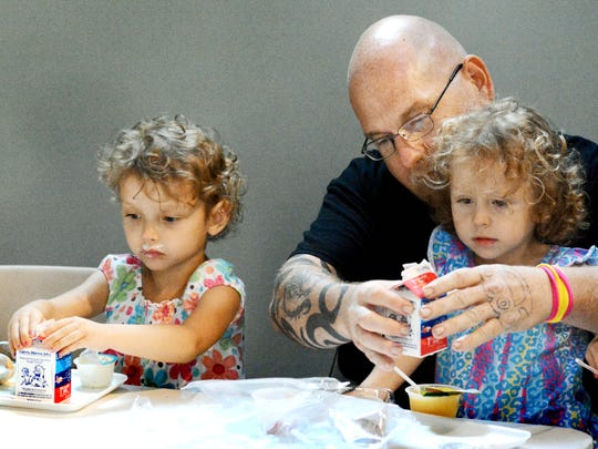 Sophia, 4, left, and sister Destiny, 3, get some help from their father J.R., while having lunch in the Summer Food Service Program at Martin Library Tuesday, July 11, 2017. The program offers free breakfast and lunch to children 18 and younger Monday through Friday. Bill Kalina photo