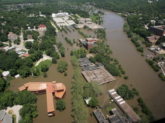 In this Monday 2008 file photo, floodwaters from the Iowa River surround the University of Iowa's art building, bottom left, in Iowa City, Iowa. The university's recovery from the flood focused attention on FEMA's so-called 50 percent rule. The agency initially promised $297 million to replace a flooded performing arts auditorium and a flooded art school building, but ruled that the school's damaged art museum should be repaired at its same location for $5.2 million.