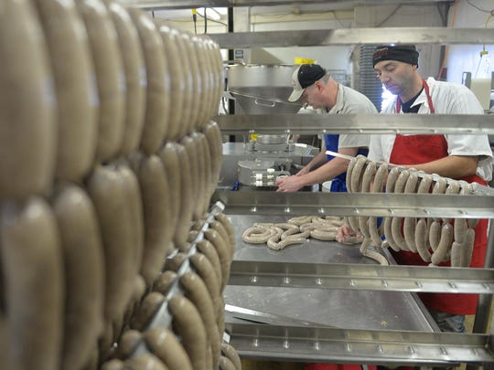 Sausage makers Chris Lichy, near, and Rick Rausch make