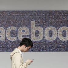 A man walks past a Facebook sign in an office on the Facebook campus in Menlo Park, Calif. In a report released Tuesday, Aug. 26, 2014, the Pew Research Center found that most people who regularly use social media sites are actually less likely to share their opinions, even offline.