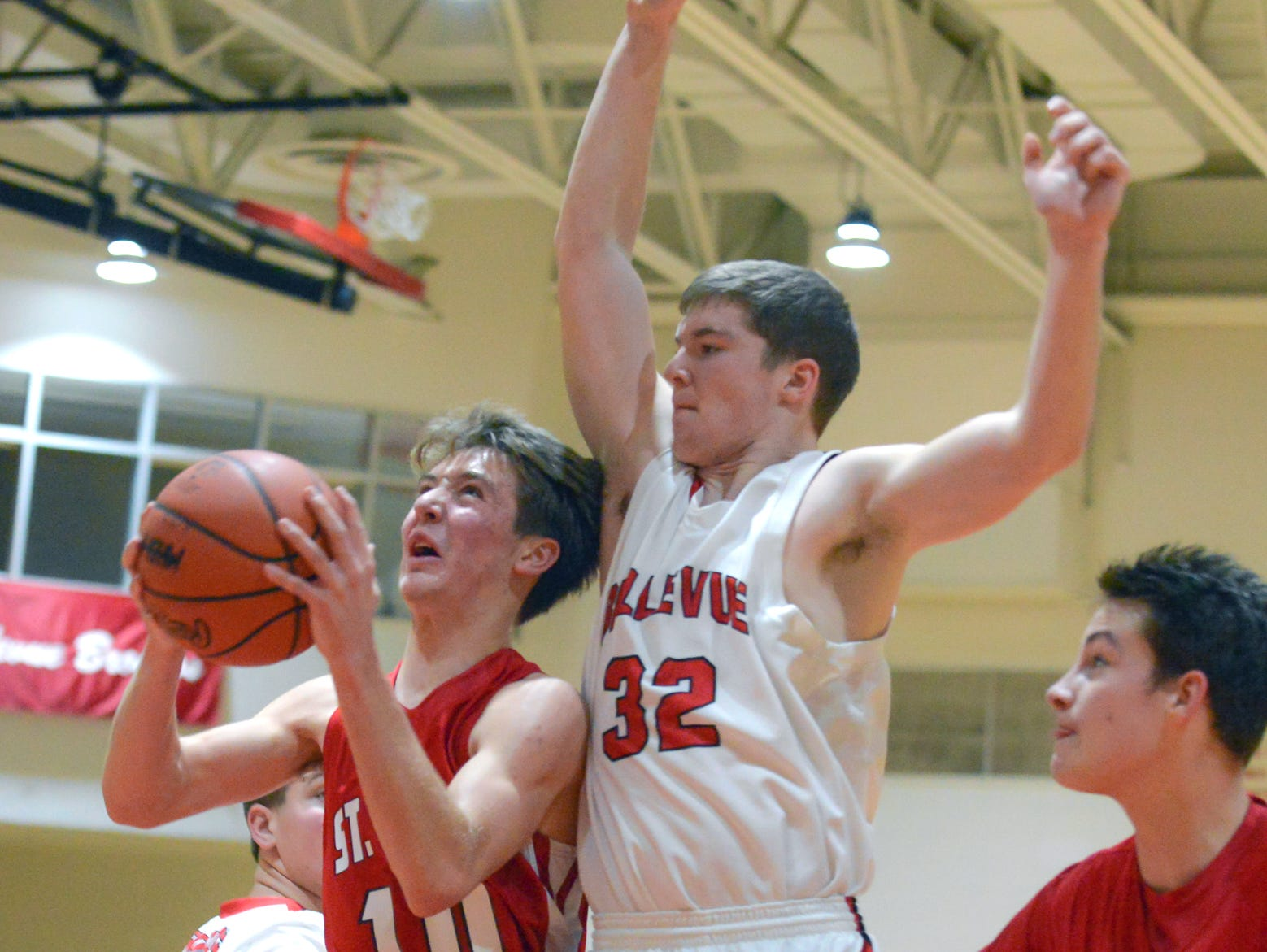 St. Philip's Ben Swagler goes for a lay-up as Bellevue's Ryan Madry works on the block.