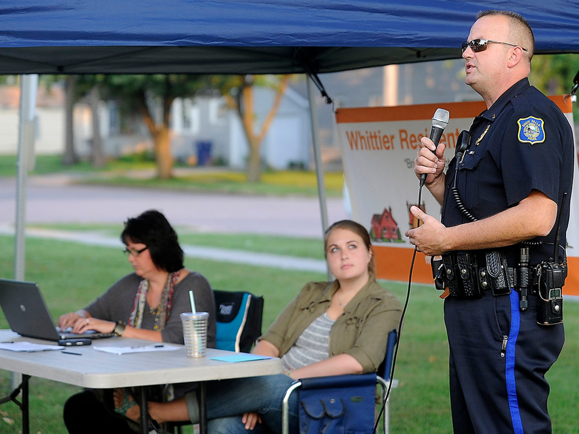 Sgt. Keith Gries talks with Whittier neighborhood residents about public safety concerns at Heritage Park in August 2015.