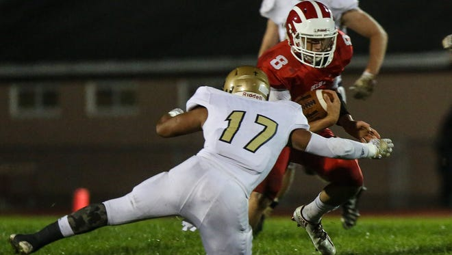 Justin Figueroa of Holy Spirit tackles Delsea quarterback Mason Maxwell during Friday's 14-7 victory.