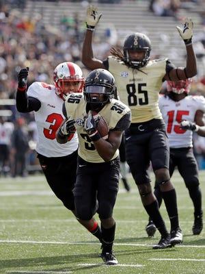 Vanderbilt wide receiver Trey Ellis (36) scores a touchdown ahead of Western Kentucky linebacker Kyle Bailey (36) after Ellis caught a pass that bounced off wide receiver Chris Pierce (85) in the first half of an NCAA college football game Saturday, Nov. 4, 2017, in Nashville, Tenn. (AP Photo/Mark Humphrey)