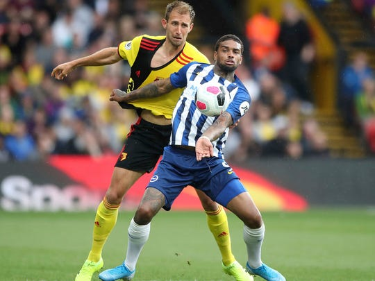 Watford's Craig Dawson, left, and Brighton and Hove Albion's Jurgen Locadia tussle for the ball during the English Premier League soccer match between Watford and Brighton and Hove Albion at Vicarage Road stadium, Watford, England. Saturday Aug, 10, 2019 (Nick Potts/PA via AP)