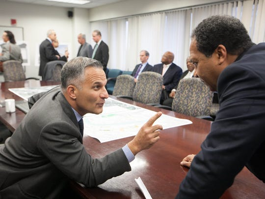 Rob Buccini (left), co-president of The Buccini/Pollin Group chats with mayor Dennis P. Williams as the mayor and his friend Ed Osborne pitch a plan to build a $25 million stadium on the Riverfront.