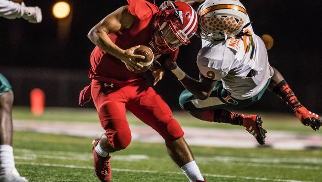 RJ Rosales gets horse collar tackled by Seneca Milledge during the Class 5A regional semifinal game against Dunbar High School in Immokalee, Fla., on Friday, Nov. 17, 2017.