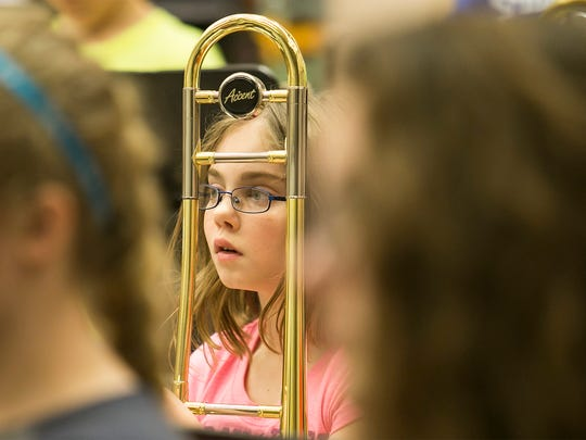 "Seen through her trombone, sixth-grader Tyler Chrushong, pays attention while receiving instructions from award-winning composer and conductor Brian Balmages Wednesday, March 16, 2016, at Spring Grove Intermediate School. The fifth- and sixth-grade band, will play ""Tears of Arizona"" publicly for the first time during a concert, held at the school on March 31, and then again in Washington D.C in May. Amanda J. Cain photo"