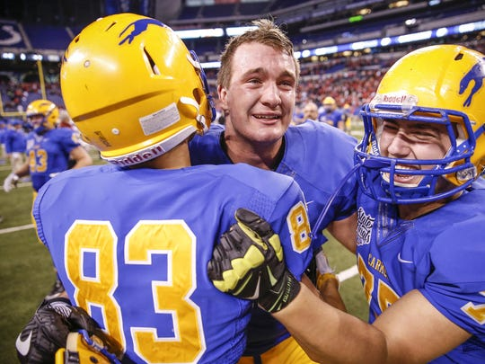 Britt Beery (center) hugs teammates after Carmel's 16-13 win against Center Grove in the Class 6A state title game at Lucas Oil Stadium on Nov. 25, 2016.