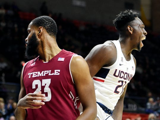 Connecticut's Mamadou Diarra (21) screams to his team after dunking over Temple's Damion Moore (23) during an NCAA college basketball game Wednesday, Feb. 28, 2018, in Storrs, Conn. Connecticut won, 72-66. (AP Photo/Stephen Dunn)