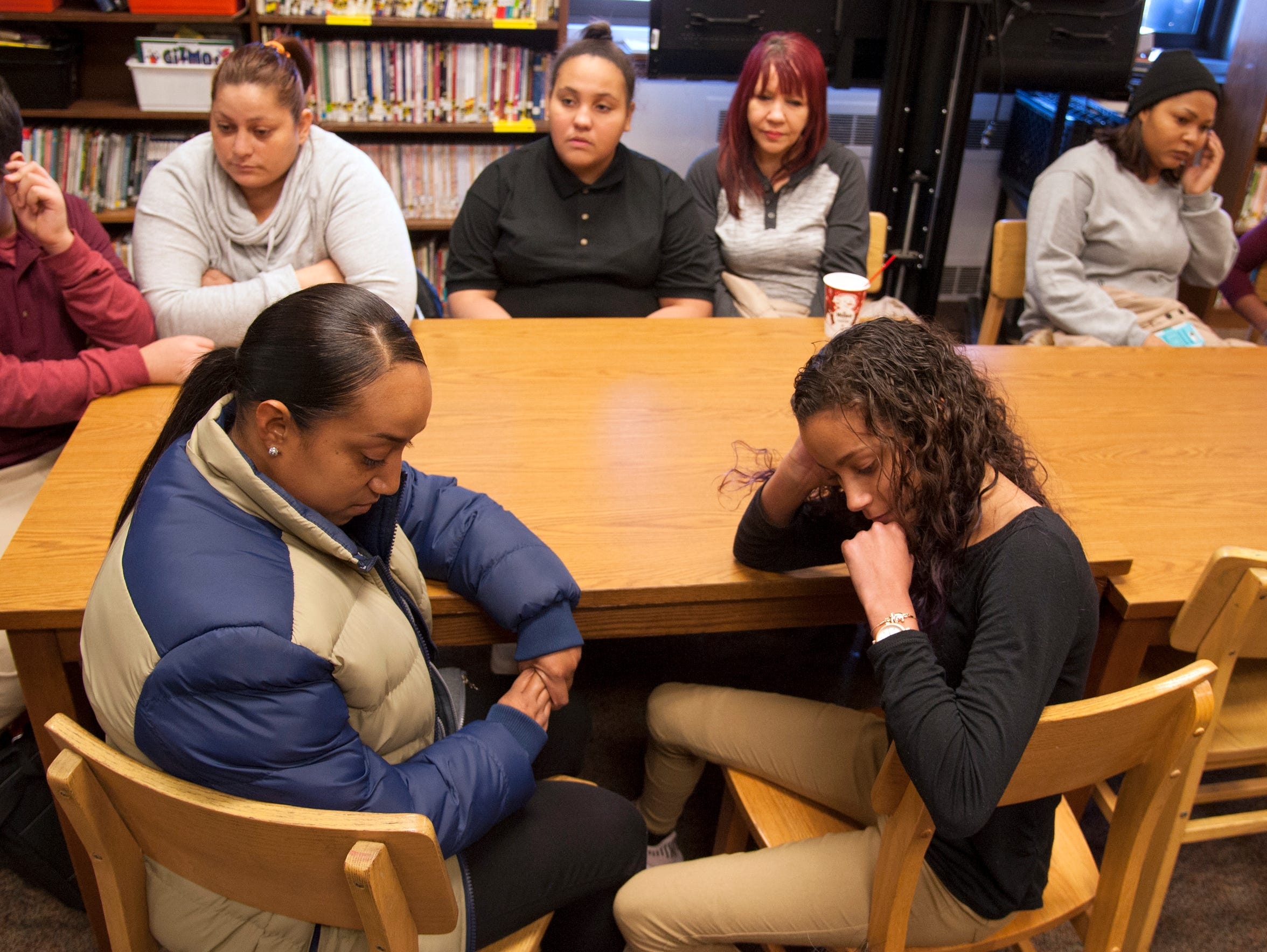 Students from Puerto Rico, who currently attend the Veteran's Memorial School in Camden after being displaced by Hurricane Maria, sit with their mothers in the school's library.
