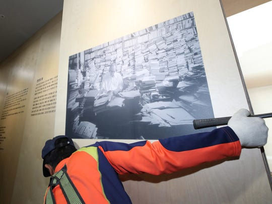 A worker removes a portrait of South Korean poet Ko