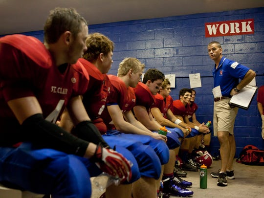 St. Clair coach Bill Nesbitt talks with players in the locker room at half time during a football game September 6, 2014 at East China Stadium.