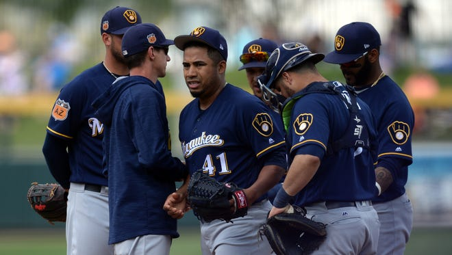 Brewers manager Craig Counsell (sweatshirt) pulls starting pitcher Junior Guerra out of the game against the Athletics during the fourth inning at HoHoKam Stadium.