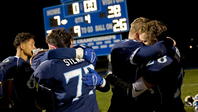 Players line up to hug the seniors after losing a regional final football game to Flint Powers Catholic Friday, November 13, 2015 at Richmond High School.