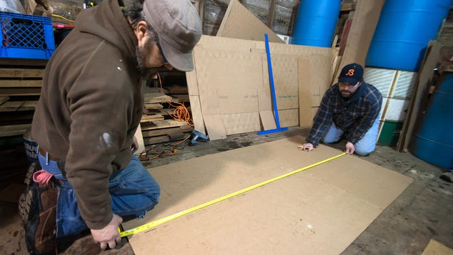 Ben Crane (left) and Ben Duval start with a fresh cardboard box as they measure out teh beginning stages of the Lego Block sled.