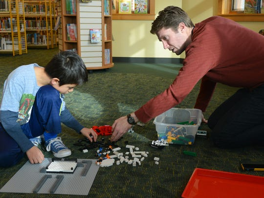 At the Willard Library Helen Warner Branch Saturday, Joshua Hennessy, 9, works with his father, Matt Hennessy, as they construct a wrestling ring out of Legos.