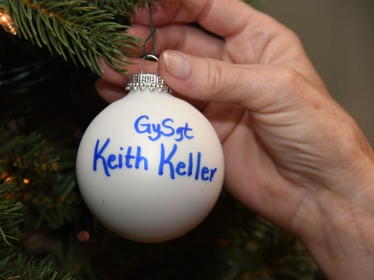 An ornament is placed on a Christmas tree at Baptist Easley's Festival of Trees to honor Gunnery Sgt. Keith Keller.