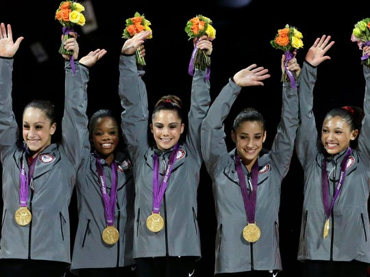 """FILE - In this July 31, 2012, file photo, U.S. gymnasts, left to right, Jordyn Wieber, Gabrielle Douglas, McKayla Maroney, Alexandra Raisman and Kyla Ross raise their hands on the podium during the medal ceremony for the Artistic Gymnastic women's team final at the 2012 Summer Olympics in London. Two-time Olympic medalist McKayla MAroney said in an interview with gymnastics podcast Gymcastic released Wednesday, Feb. 24, 2016, that she's stepping away from competition but not """"retiring"""" from the sport. """"Fierce Five"""" teammate Kyla Ross announced her retirement from elite competition on Monday. (AP Photo/Gregory Bull, File)"""